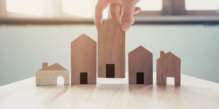 Hand choosing wooden house model, Mortgage and real estate property investment